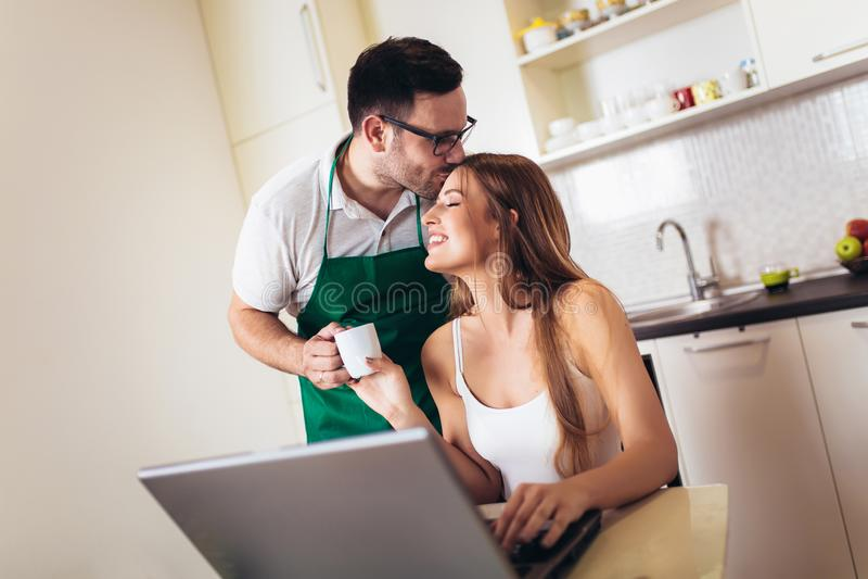 Woman working on laptop in kitchen as boyfriend prepares meal royalty free stock photos