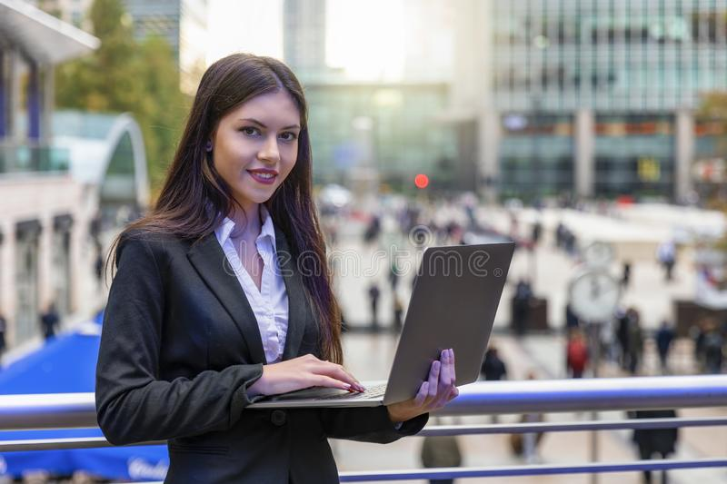Woman working on a laptop outdoors in Canary Wharf, UK. Attractive woman in corporate outfit working on a laptop outdoors in a financial district of London stock image