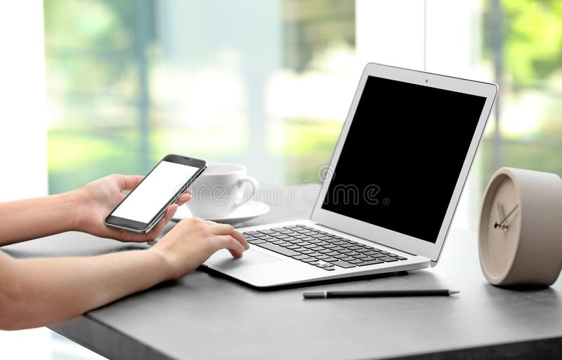 Woman working with laptop and smartphone royalty free stock photo