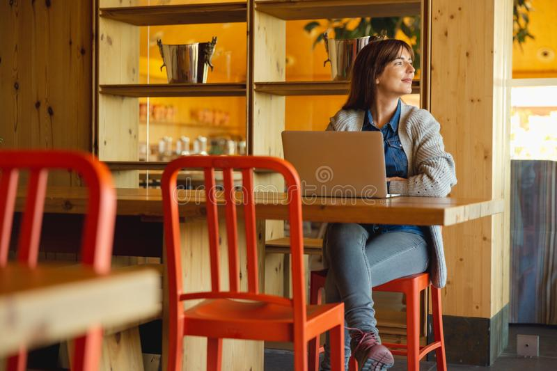 Woman working on a laptop. On a cozy space royalty free stock photos