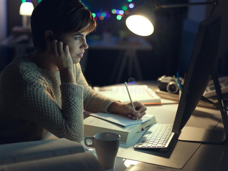 Woman working late at night stock images