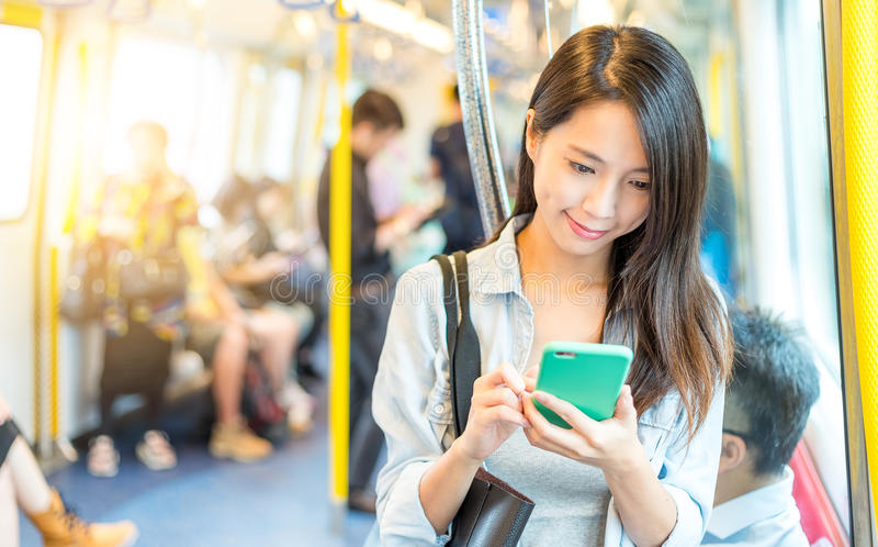 Woman working on mobile phone inside train compartment stock images
