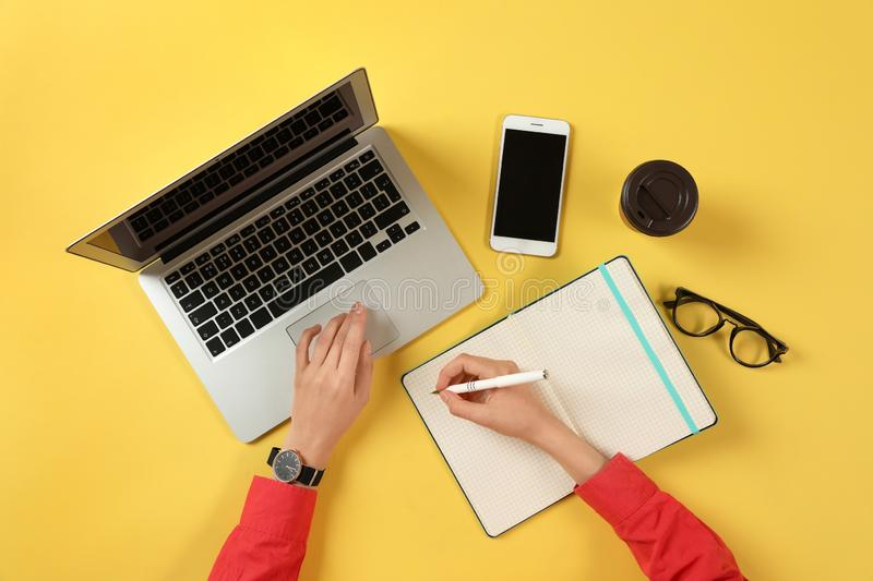 Woman working with modern laptop and writing in notebook at color table. Top view royalty free stock photos