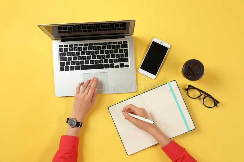 Woman working with modern laptop and writing in notebook at color table. Top view royalty free stock photo