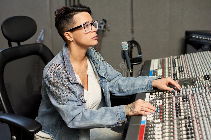 Woman working on music control console stock image