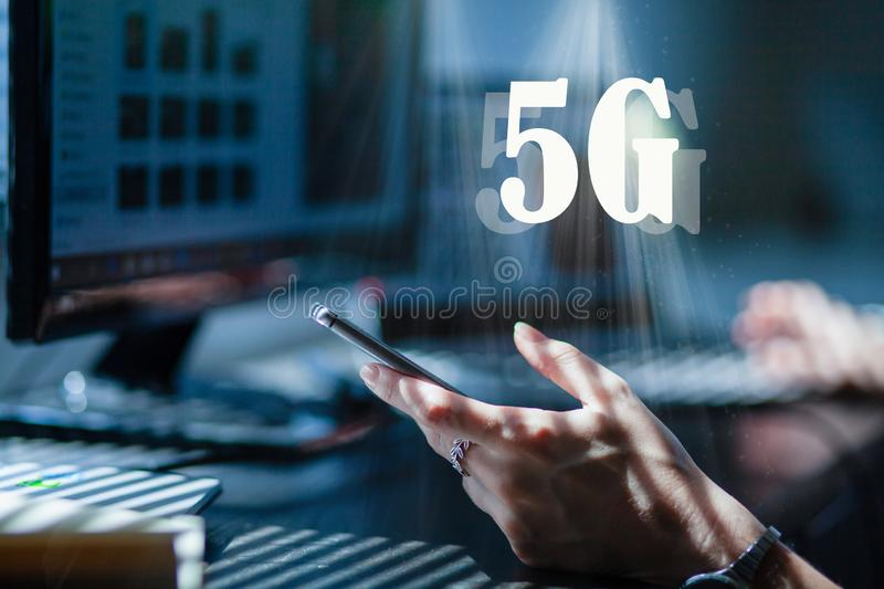 woman working in an office or home office using 5G technology - hand holding smartphone, laptop and monitor in the background stock photography