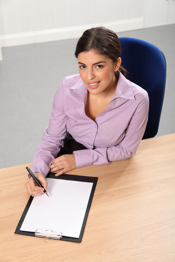 Download Woman Working In Office Looks Up While Writing Stock Photo - Image: 17433124