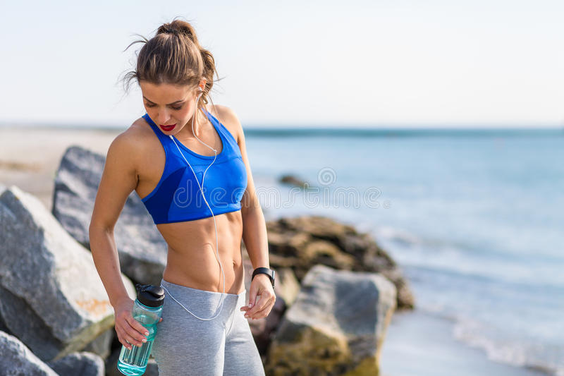 Woman working out at the beach. Woman working out outdoors in the summer at the beach stock photo