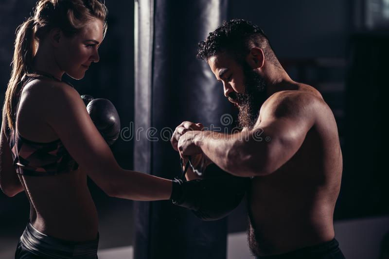 Woman working out with boxing gloves and punching bag with her trainer. stock image