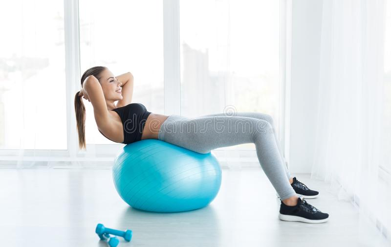 Woman working out with fitness ball in gym royalty free stock photography