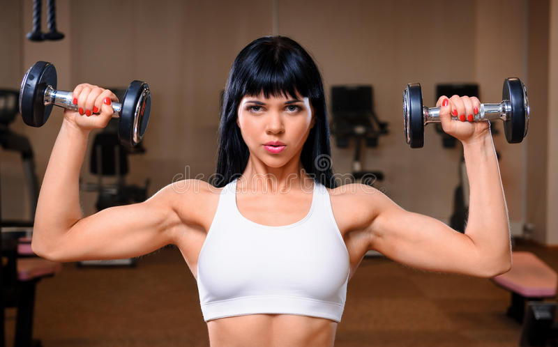 Woman working out in fitness club royalty free stock photo