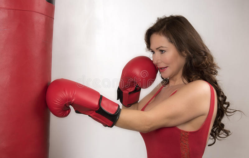 Woman working out with gloves and a punchbag. Woman boxer wearing red boxing gloves using a punchbag to workout royalty free stock photos