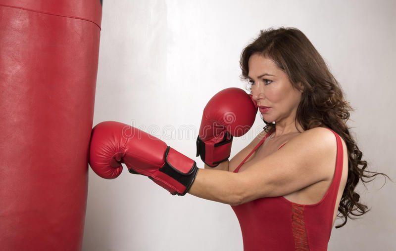 Woman working out with gloves and a punchbag. Woman boxer wearing red boxing gloves using a punchbag to workout royalty free stock photo