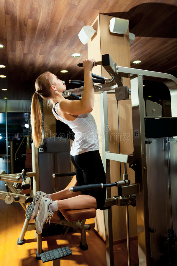 Woman working out in gym - pull ups.  stock image