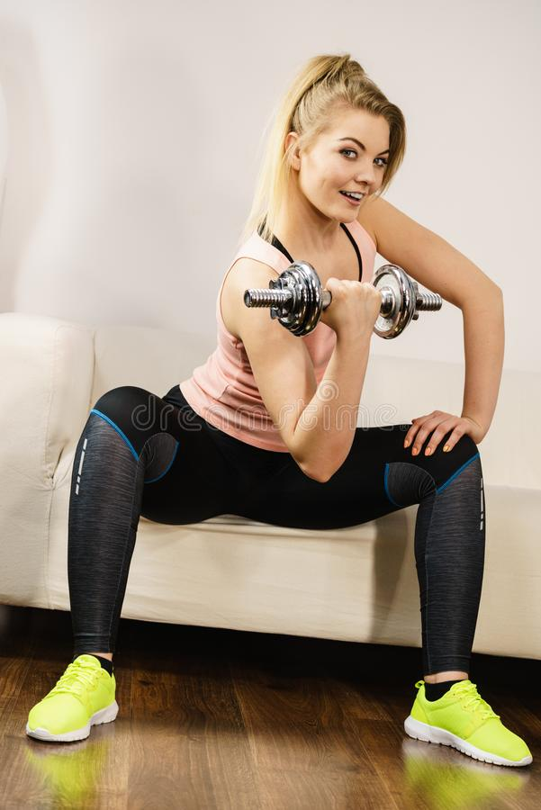 Woman working out at home with dumbbell stock photography