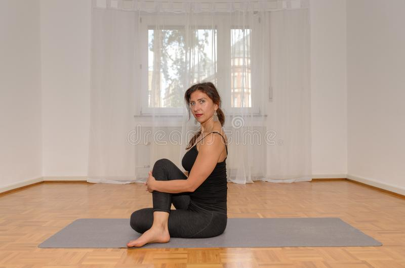 Woman working out at home on a mat. On the floor preparing to start in a health and fitness concept stock image