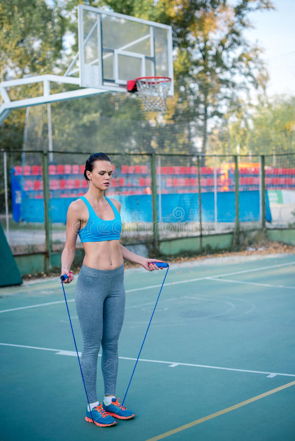 Woman working out with skipping rope. Attractive woman working out with skipping rope on the stadium stock photos