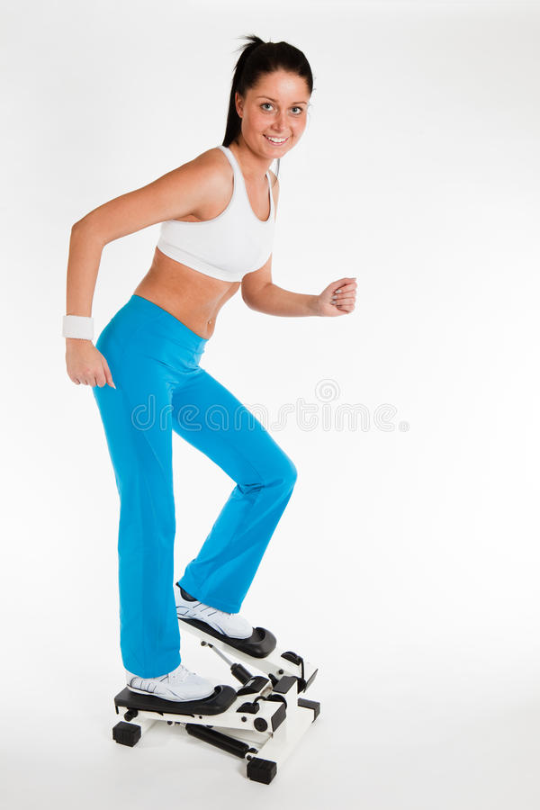 Woman working out on stepper trainer. Young woman exercising on stepper trainer, vertical royalty free stock photos