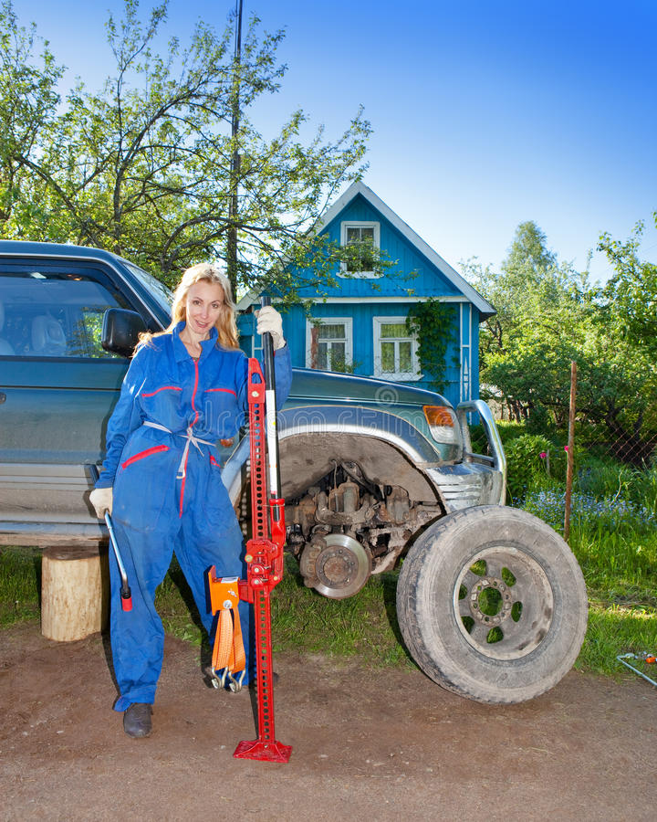 Download The Woman In Working Overalls Tries To Replace A Wheel At An Off-road Car Stock Photo - Image: 30573592