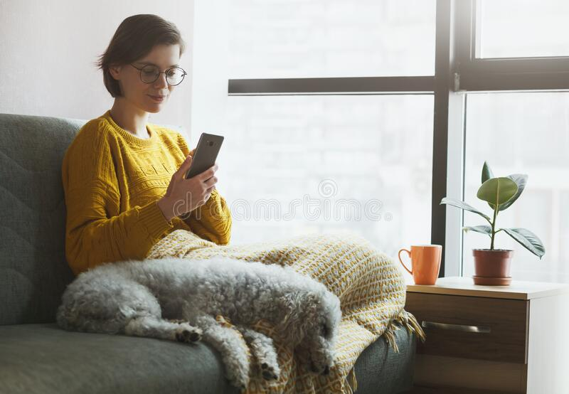 Woman working with phone at home quarantine. stock image