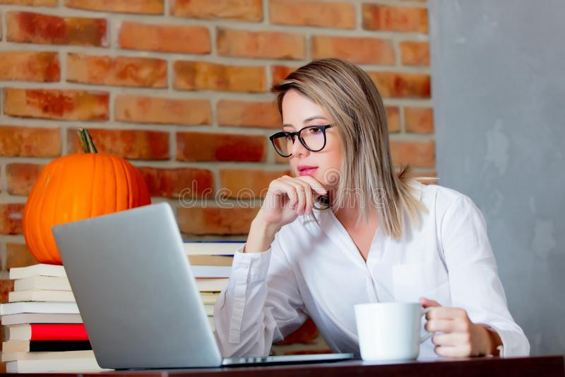 Woman on working place holding a cup of hot drink. Young businesswoman sitting on working place with laptop computer and books holding a hot drink. Brick wall on royalty free stock photos