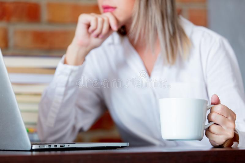 Woman on working place holding a cup of hot drink. Young businesswoman sitting on working place with laptop computer and books holding a hot drink. Brick wall on royalty free stock image