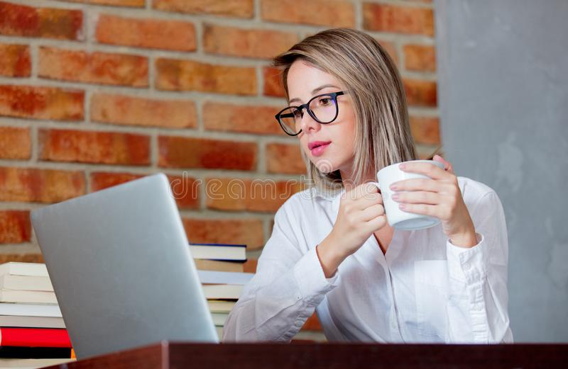 Woman on working place holding a cup of hot drink. Young businesswoman sitting on working place with laptop computer and books holding a hot drink. Brick wall on royalty free stock images