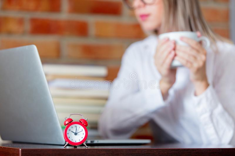 Woman on working place holding a cup of hot drink. Young businesswoman sitting on working place with laptop computer and books holding a hot drink. Alarm clock royalty free stock photo