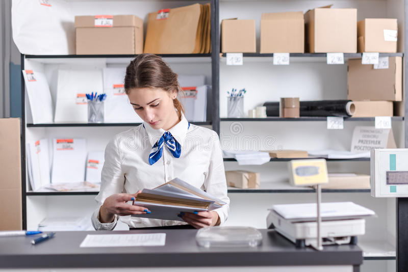 Woman working at the post office. Young woman working at the post office royalty free stock photos