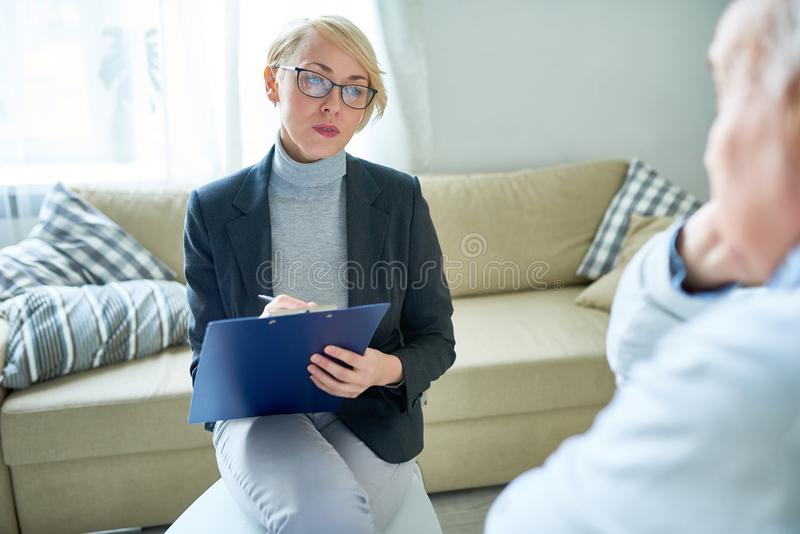 Woman working with senior patients in nursing home. Adult women in glasses taking notes on clipboard talking to elderly people in assisted living center royalty free stock photos