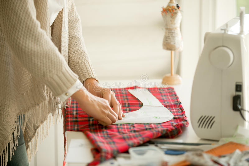 Woman working with a sewing pattern stock photography