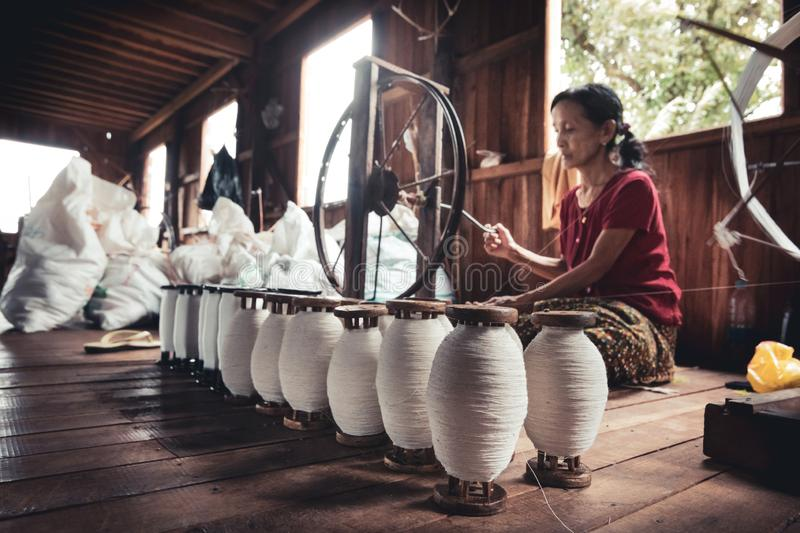 Woman working, sitting on the ground, the lotus thread. royalty free stock images