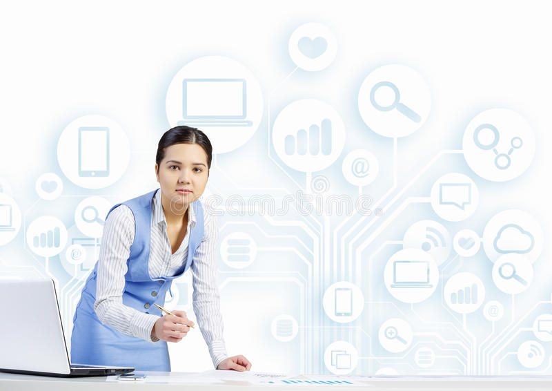 Woman working at table. Young businesswoman at desk with laptop and cloud computing concept on background stock image