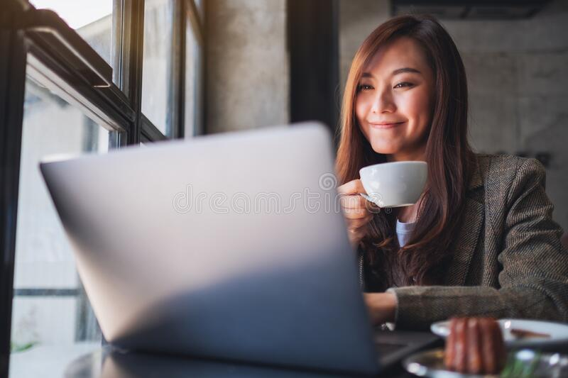 A woman working and typing on laptop computer while drinking coffee in cafe royalty free stock images