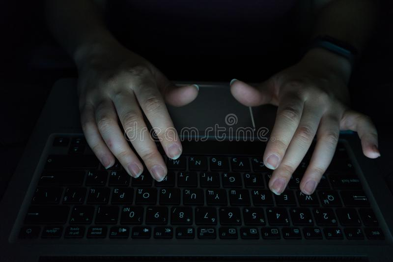 woman is working typing use laptop at dark night. Hands in the keyword with computer above typing. Late internet addiction or royalty free stock image