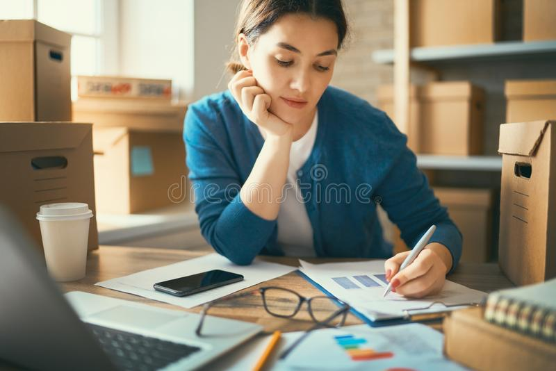 Woman is working at warehouse for online store stock photography
