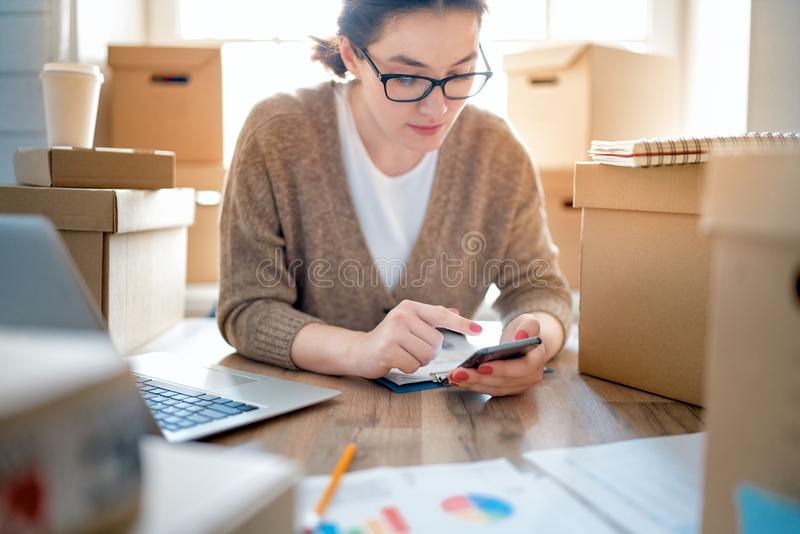 Woman is working at warehouse for online store. Woman is working at warehouse for online seller. Concept of small web business stock image