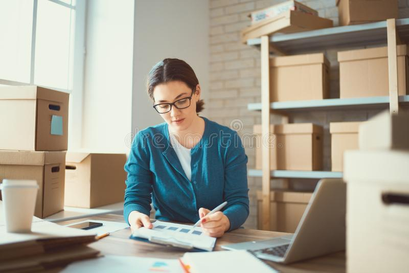 Woman is working at warehouse for online store. Woman is working at warehouse for online seller. Concept of small web business royalty free stock image