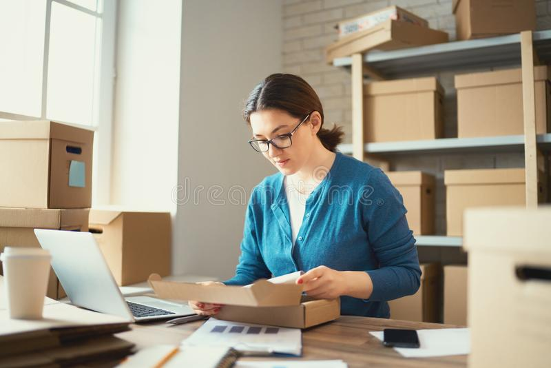 Woman is working at warehouse for online store. Woman is working at warehouse for online seller. Concept of small web business royalty free stock photo