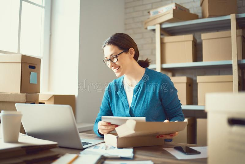 Woman is working at warehouse for online store. Woman is working at warehouse for online seller. Concept of small web business stock images
