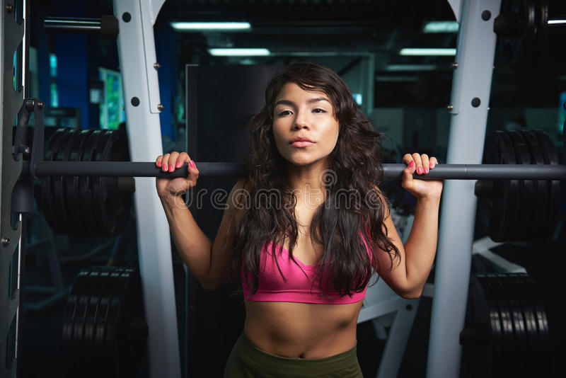 Woman workout with barbell. In gym. girl with barbell in fitness club doing exercise royalty free stock photo