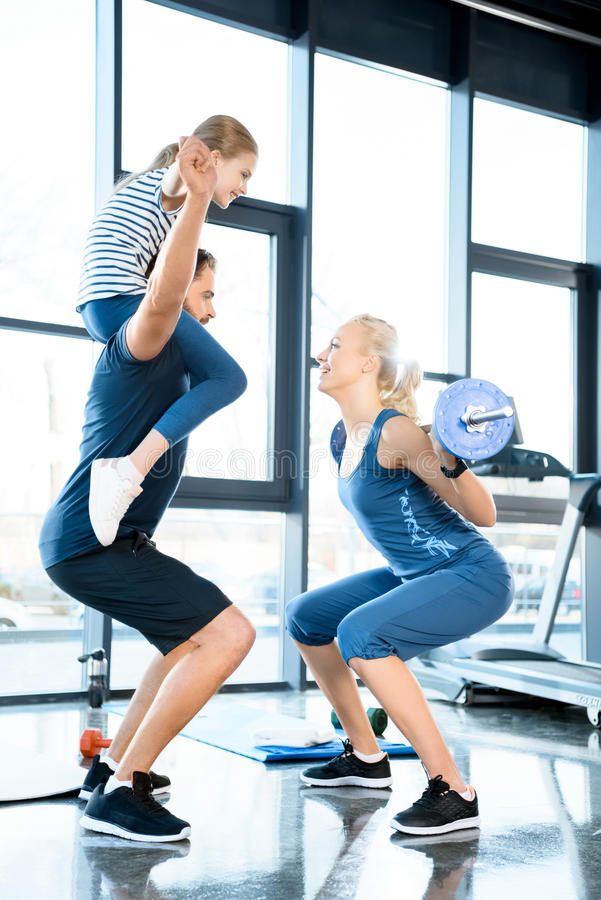 Woman workout with barbell while man having fun with daughter on his shoulders. Woman workout with barbell while men having fun with daughter on his shoulders in stock photos