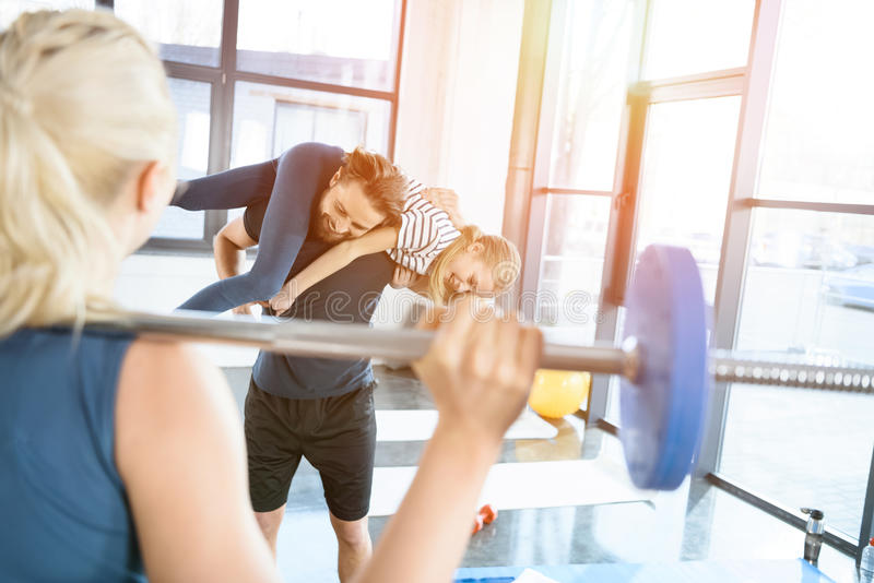 Woman workout with barbell while man having fun with daughter on his shoulders. Woman workout with barbell while men having fun with daughter on his shoulders in royalty free stock photos