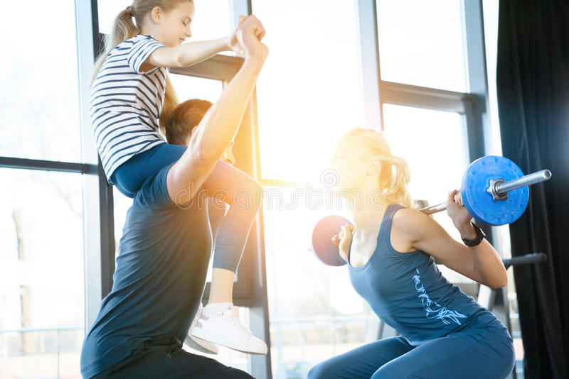 Woman workout with barbell while man having fun with daughter on his shoulders. Woman workout with barbell while men having fun with daughter on his shoulders in royalty free stock image