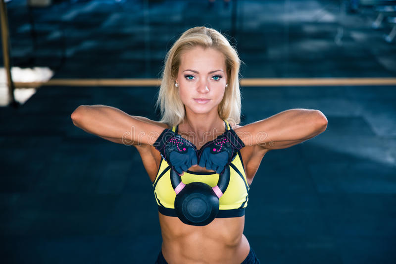 Woman workout with kettle ball in gym. Beautiful sporty woman workout with kettle ball in gym royalty free stock photography