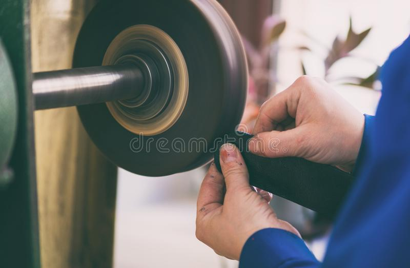 Woman works on a grinding machine. She grinds one piece of leather stock images