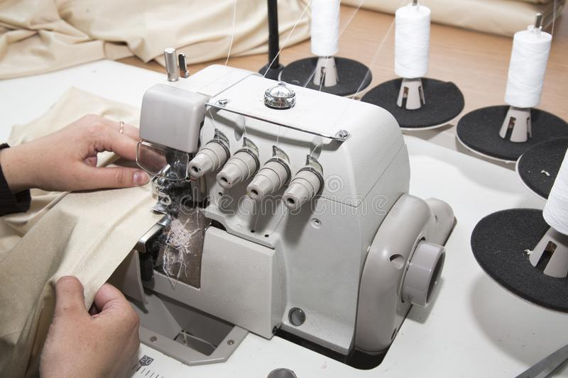 Woman works on overlock royalty free stock images