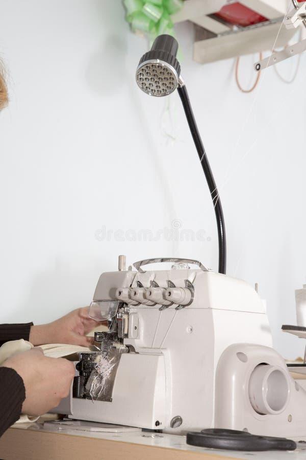 Woman works on overlock royalty free stock image