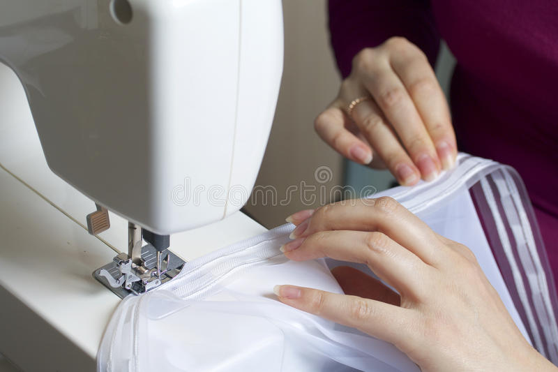 A woman works on a sewing machine. She sews the curtains on the window royalty free stock photography