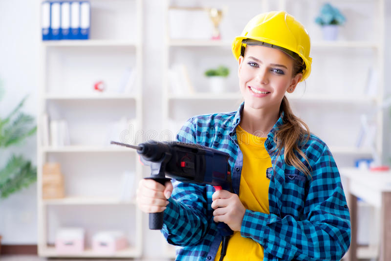 The woman in workshop with drilling drill royalty free stock photography